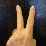 V for Victory top of hand should face individual making sign
